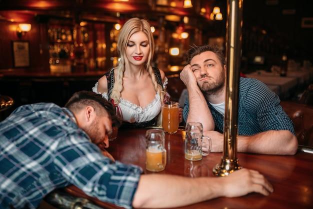 Dwóch pijanych przyjaciół śpiących przy ladzie z kuflami piwa w pubie, ładna kelnerka