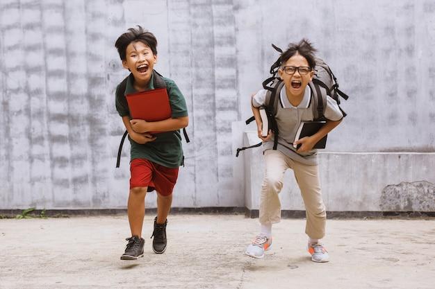 Dwóch podekscytowanych azjatyckich uczniów wita z powrotem w szkole po pandemii