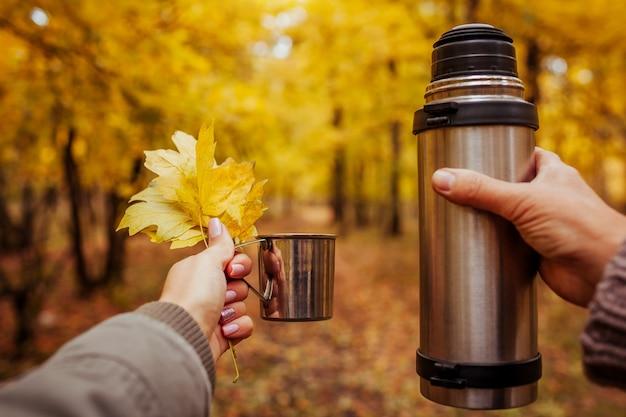 Dwóch podróżników odpoczywających i pijących herbatę w jesiennym lesie