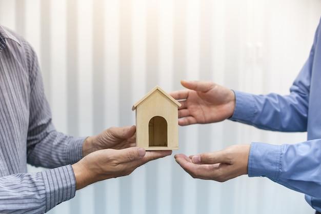 Dwóch pośredników w obrocie nieruchomościami trzyma modele domu w biurze