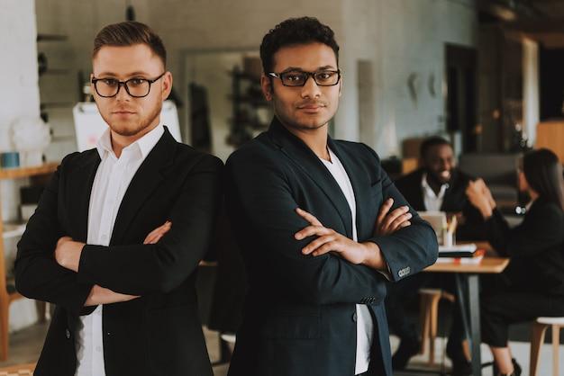 Dwóch poważnych biznesmenów z skrzyżowanymi rękami.