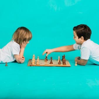 Dwóch poważnych chłopców grających w szachy na niebieskim tle