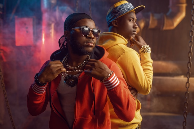 Dwóch poważnych raperów tańczących breakdance z fajną undergroundową dekoracją. wykonawcy hip-hopu, modni rapujący, breakdance