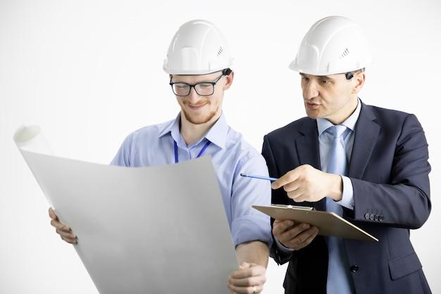 Dwóch pozytywnych inżynierów budowlanych patrzy na rysunek