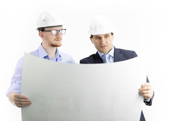 Dwóch pozytywnych inżynierów patrzy na rysunek, szef daje instrukcje podwładnym