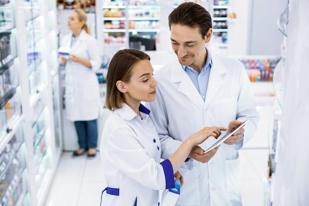 Dwóch pracowników apteki w białych fartuchach stoi i omawia szereg leków