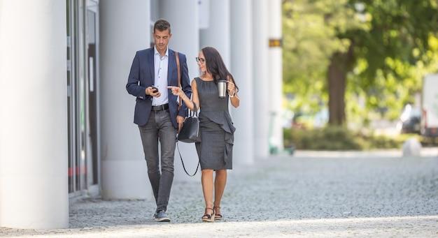 Dwóch pracowników biurowych idzie do pracy, omawiając wiadomości przez telefon komórkowy.