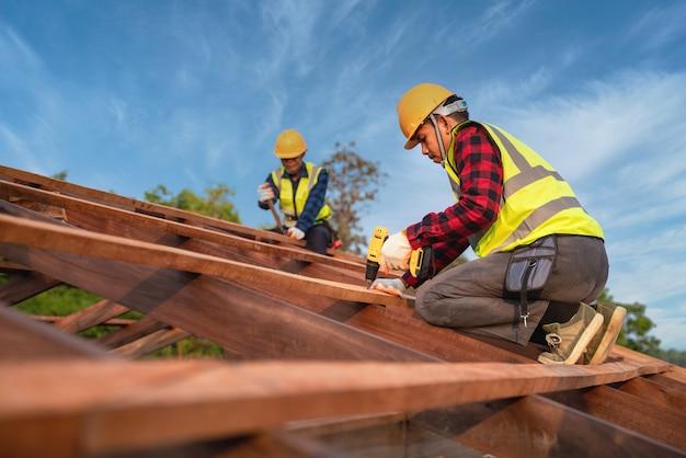 Dwóch pracowników budowlanych instaluje nowy dach, narzędzia dekarskie, wiertarka elektryczna używana na nowych dachach o drewnianej konstrukcji dachu, koncepcja budowy pracy zespołowej.