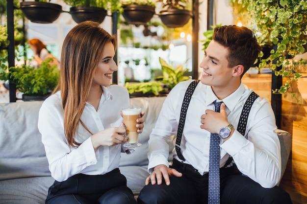 Dwóch pracowników dyskutuje o swojej pracy przy przerwach na kawę w kawiarni