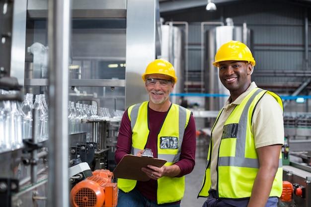Dwóch pracowników fabrycznych dyskutujących podczas monitorowania linii produkcyjnej napojów