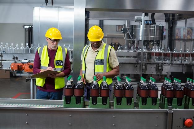 Dwóch pracowników fabrycznych monitorujących butelki zimnego napoju w zakładzie