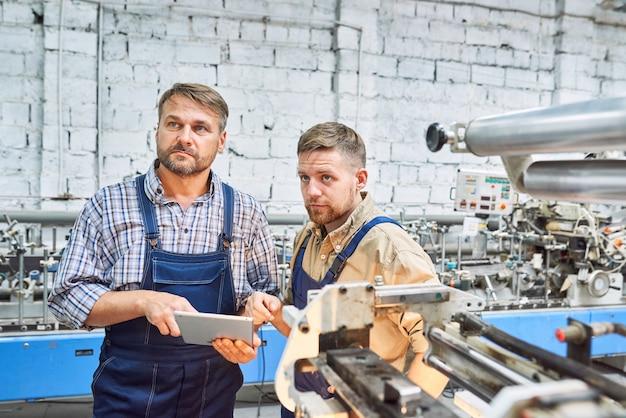 Dwóch pracowników fabrycznych obsługujących nowoczesną maszynę