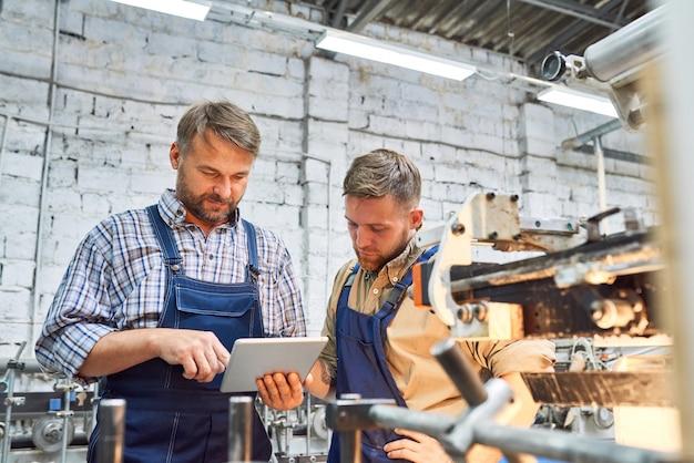 Dwóch pracowników fabrycznych obsługujących nowoczesny sprzęt