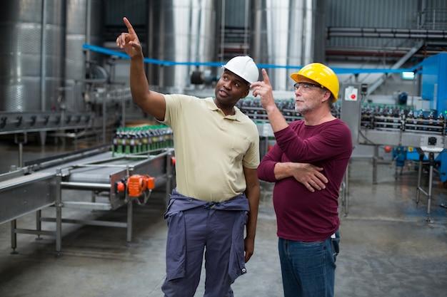 Dwóch pracowników fabrycznych skierowanych w górę podczas wspólnej dyskusji