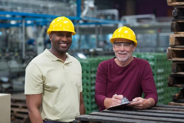 Dwóch pracowników fabrycznych stojących ze schowkiem w zakładzie produkcji napojów