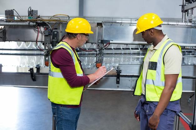Dwóch pracowników fabrycznych ze schowkiem pracujących obok linii produkcyjnej