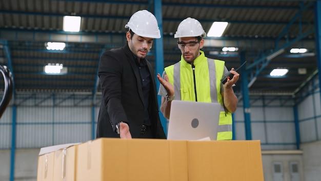 Dwóch pracowników fabryki pracuje i omawia plan produkcji w fabryce. koncepcja przemysłu i inżynierii.