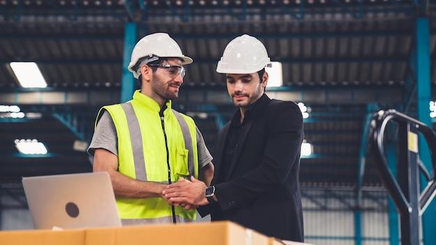 Dwóch pracowników fabryki pracuje i omawia plan produkcji w fabryce