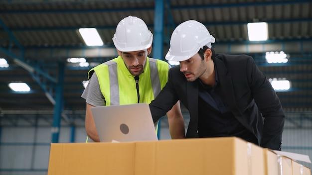 Dwóch pracowników fabryki pracuje i omawia plan produkcji w fabryce.
