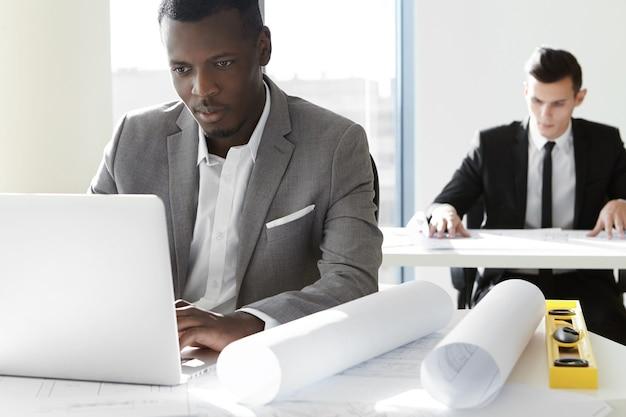 Dwóch pracowników firmy budowlanej pracujących w biurze