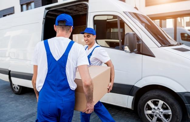 Dwóch pracowników firmy przeprowadzkowej ładuje pudła do minibusa