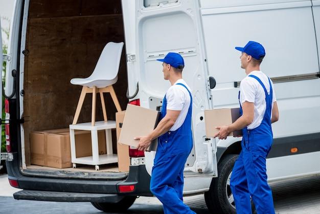 Dwóch pracowników firmy przeprowadzkowej ładuje pudła i meble do minibusa