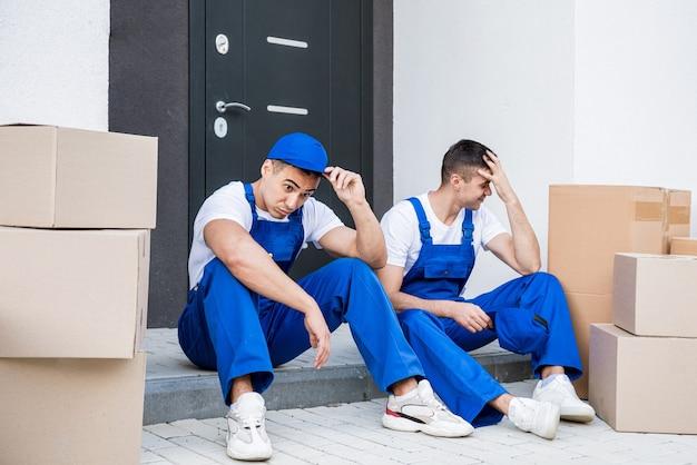 Dwóch pracowników firmy przeprowadzkowej ma przerwę podczas siedzenia na schodku