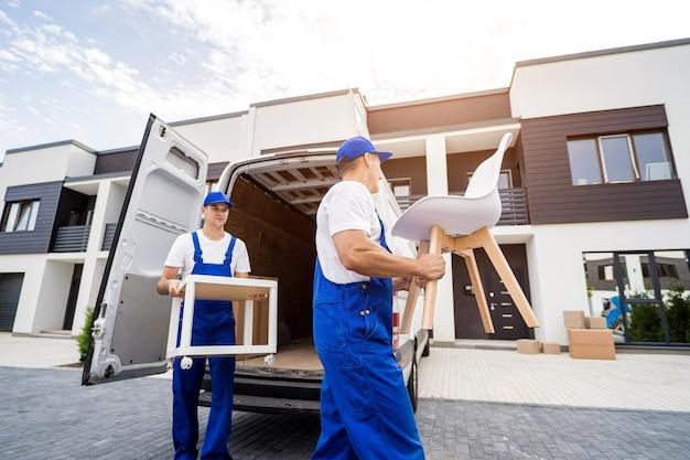 Dwóch pracowników firmy przeprowadzkowej rozładowujących skrzynie i meble z minibusa