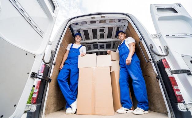 Dwóch pracowników firmy przeprowadzkowej rozładowujących skrzynie z minibusa