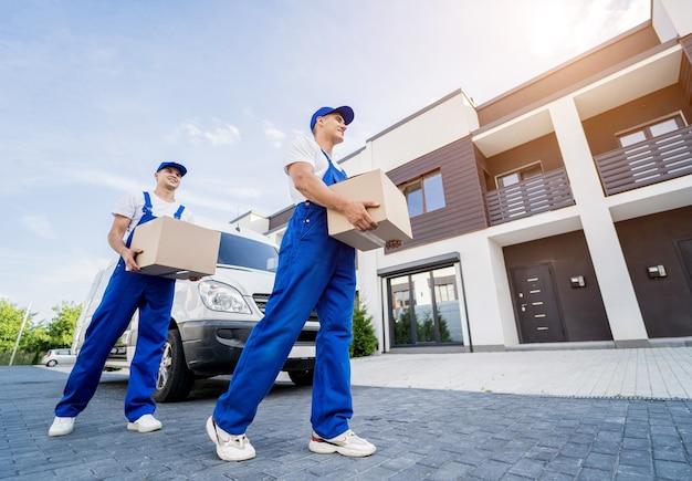 Dwóch pracowników firmy przeprowadzkowej rozładowuje pudełka z minibusa do domu klienta