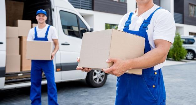 Dwóch pracowników firmy przeprowadzkowej rozładowuje pudła z minibusa do nowego domu