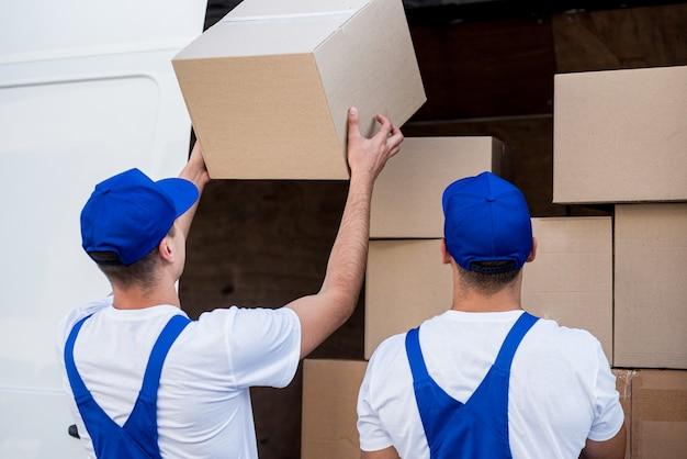 Dwóch pracowników firmy przeprowadzkowej rozładowuje skrzynie z minibusa do nowego domu