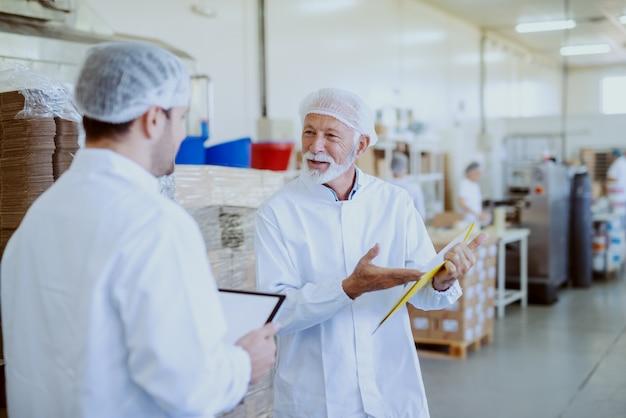 Dwóch pracowników kontroli jakości w sterylnych białych mundurach porównujących dane. starszy wskazuje na dokumenty w folderze, a młodszy trzyma tablet. wnętrze zakładu spożywczego.
