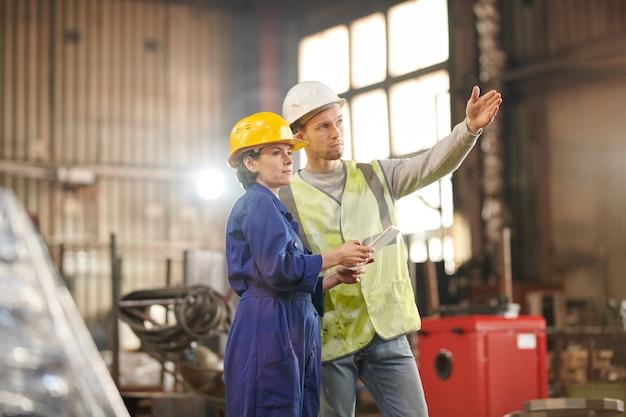 Dwóch pracowników kontrolujących fabrykę