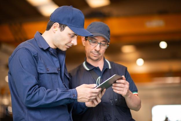 Dwóch pracowników korzystających z tabletu w nowoczesnej fabryce