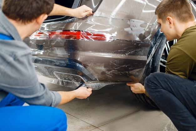 Dwóch pracowników nakłada folię ochronną na tylny zderzak. montaż powłoki chroniącej lakier samochodu przed zarysowaniami. nowy pojazd w garażu, procedura tuningu
