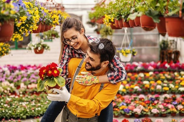 Dwóch pracowników ogrodnictwa żłobka na barana. kobieta, dając człowiekowi garnek z kwiatami.