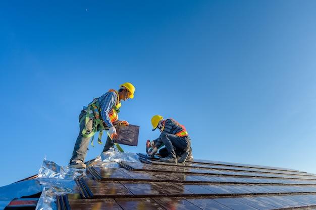 Dwóch pracowników płci męskiej ubranych w odzież ochronną montaż domu z dachówki to jest dach z dachówki ceramicznej na placu budowy