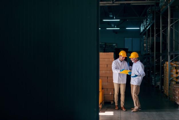 Dwóch pracowników rasy kaukaskiej dyskutuje, podczas gdy młodszy pracownik trzyma dokumenty. wnętrze magazynu.