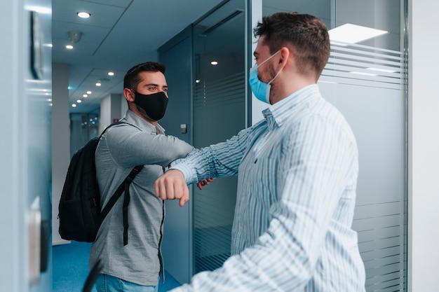 Dwóch pracowników rasy kaukaskiej z biura technologicznego w maskach na twarz