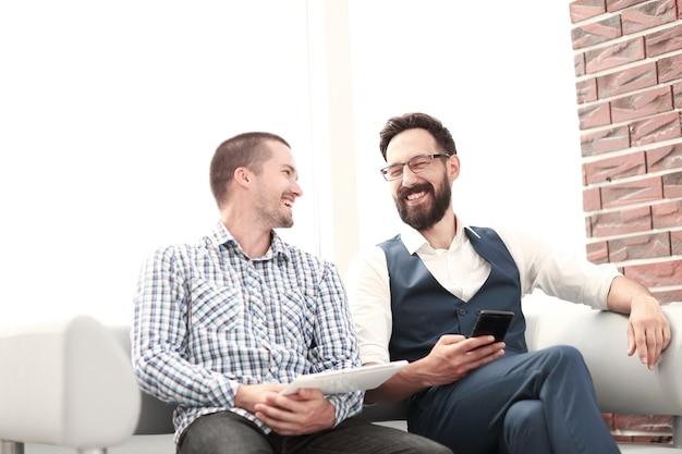Dwóch pracowników siedzących na korytarzu biurowym.zdjęcie z miejscem na kopię