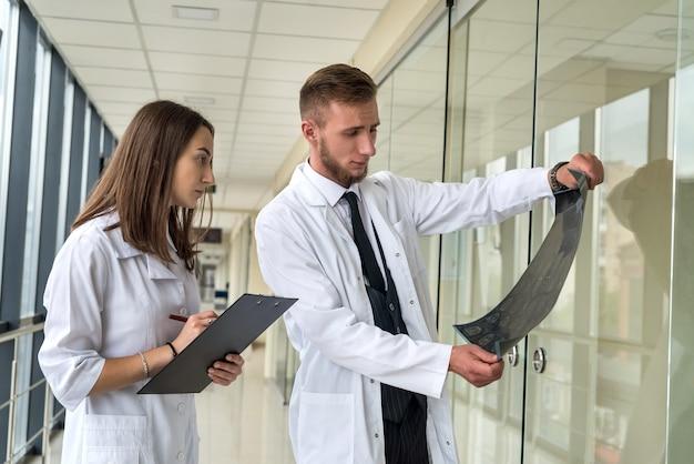 Dwóch pracowników służby zdrowia patrzących na zdjęcie rentgenowskie, rezonans magnetyczny mózgu pacjenta w celu diagnozy i leczenia w szpitalu