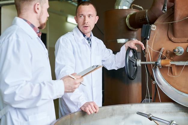 Dwóch pracowników stojących przy maszynie do pieczenia