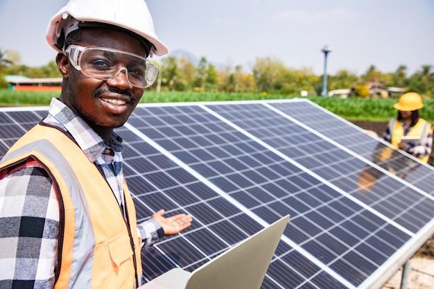 Dwóch pracowników techników instalujących ciężkie słoneczne panele fotowoltaiczne na wysokiej stalowej platformie na polu kukurydzy. pomysł na moduł fotowoltaiczny dla czystej energii