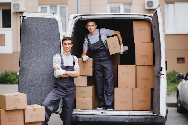 Dwóch pracowników w mundurach rozładowuje furgonetkę pełną pudeł