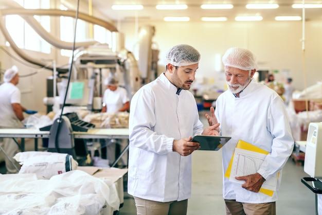 Dwóch pracowników w sterylnych białych mundurach stojących w fabryce żywności i patrząc na tablet. starszy zawiera folder ze statystykami.