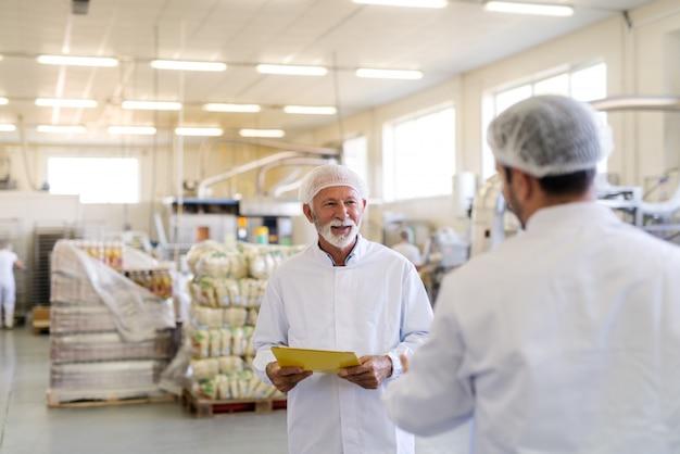 Dwóch pracowników w sterylnych mundurach mówi o jakości produktów. wnętrze fabryki żywności. selektywne skupienie się na brodaty starszy pracownik.