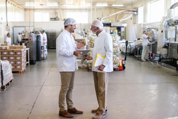 Dwóch pracowników w sterylnych mundurach rozmawia o jakości jedzenia stojąc w fabryce żywności. młodszy jeden trzyma tablet, podczas gdy starszy trzyma folder z dokumentami.