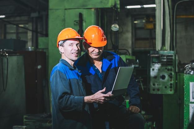 Dwóch pracowników zakładu produkcyjnego z laptopem w ręku na tle sprzętu