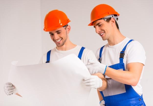 Dwóch pracujących mężczyzn stoi i patrzy na plan.